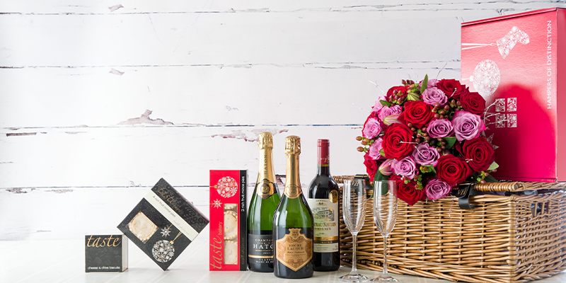 Corporate gifts arranged together, including flowers, chocolates, wines, and biscuits.